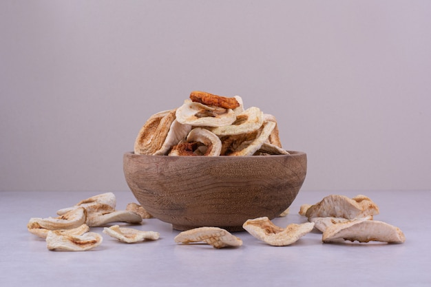 Dry apple slices in a wooden cup on grey surface