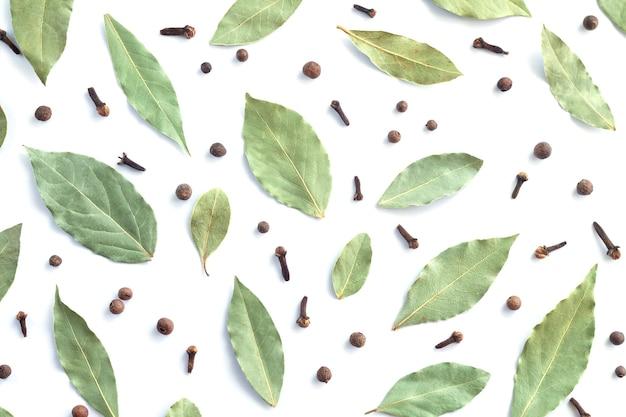 乾燥した月桂樹の葉または月桂樹、黒コショウ、クローブの上面図。料理用スパイスのフラットレイ