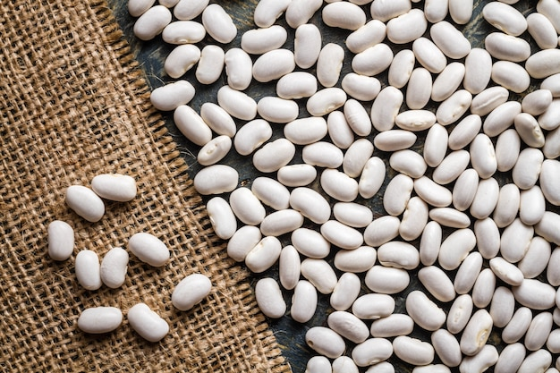 Dry beans on blue wooden table and natural burlap fabric sheet