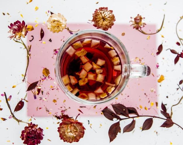 分離された灰色とピンクの表面に花とお茶のカップとドライベリスハーブ。影なし