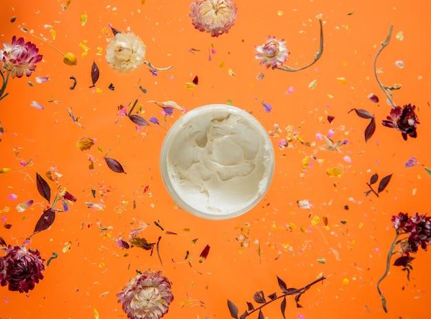 꽃과 절연 오렌지 배경에 스킨 케어 크림과 함께 건조 bellis 허브. 그림자없이
