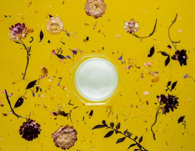 꽃과 절연 노란색 배경에 피부 케어 크림과 함께 건조 bellis 허브. 그림자없이