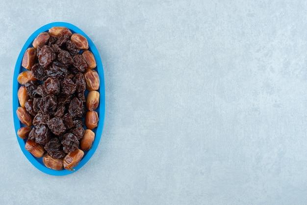 ブラックチェリーとナツメの果実を青い大皿に入れて乾かします。高品質の写真