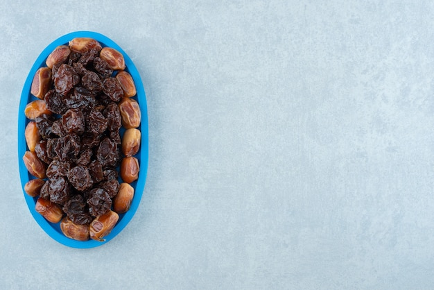 Dry black cherries and jujube berries in a blue platter. high quality photo