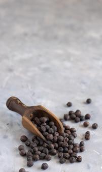 コピースペース、クローズアップと灰色のテーブルの上の木製のスクープでイタリアのプーリアとバジリカータからの乾燥した黒いひよこ豆