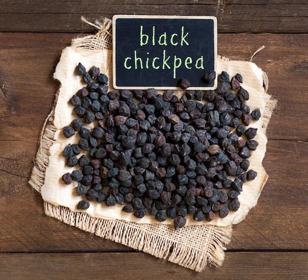 茶色の木製テーブルトップビューに小さな黒板で黒ひよこ豆を乾燥します。