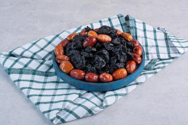 Сушеные черные сливы и финики в синем блюде.