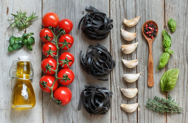 Dry black tagliatelle pasta with cherry tomatoes, garlic and herbs on wooden table top view