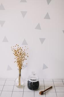 Сухой черный чай в стеклянной банке и веретено меда на кухонном фоне
