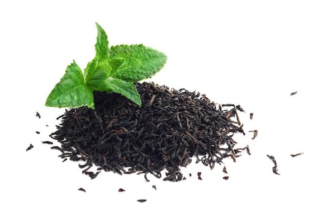 Сухие листья черного чая и мята, изолированные на белом фоне