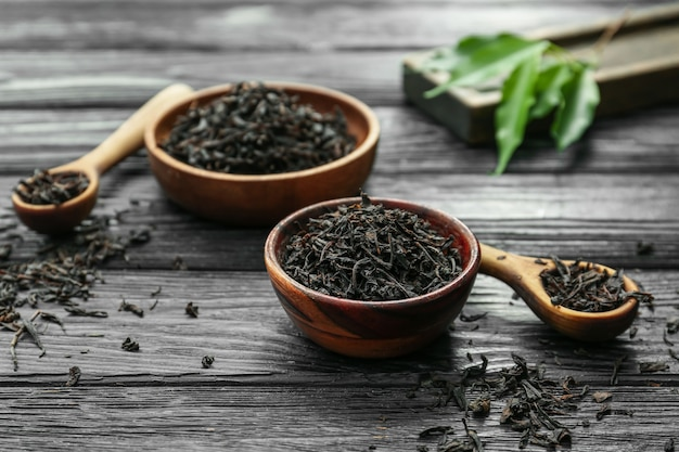 Dry black tea leaves in bowls and spoons on wooden table