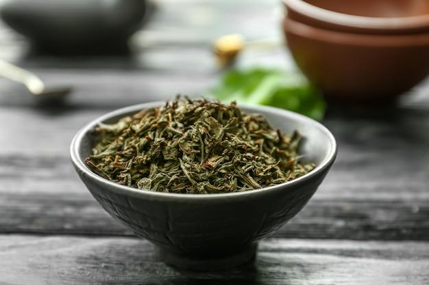 木製の背景のボウルに乾燥紅茶の葉