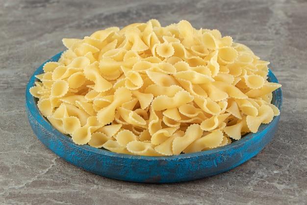 Сухие макаронные изделия лук на синей тарелке.
