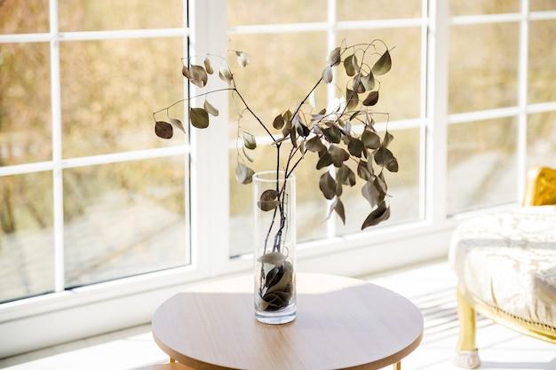 Сухая ветка с листьями в стеклянной вазе на белом столе перед большим окном.