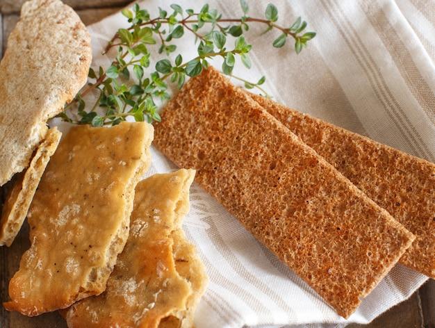 ナプキンと木製トレイの上面図にハーブと乾燥パン