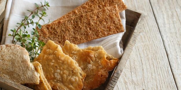 ナプキンと木製トレイにハーブと乾いたパン