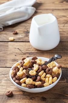 ドライブレックファーストシリアル。プレートにミルクを入れた天然シリアルから作られたチョコレートとコーンのリング。木製の素朴な背景、コピースペース。