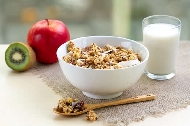 Dry breakfast cereals. crunchy honey muesli bowl with flax seeds, cranberries and coconut and a glass of milk on a table. healthy and fiber food. breakfast time