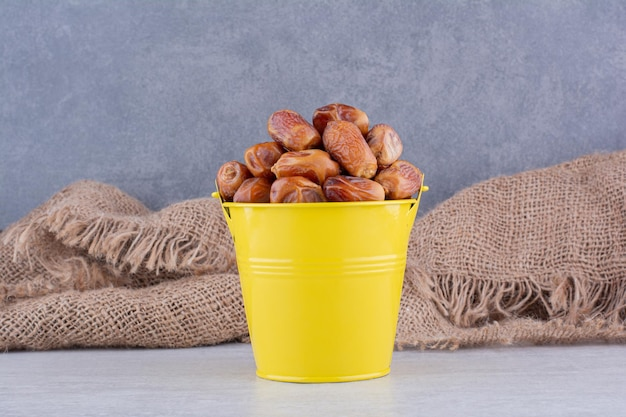 コンクリートの背景にカップの乾燥した茶色のナツメヤシ。高品質の写真