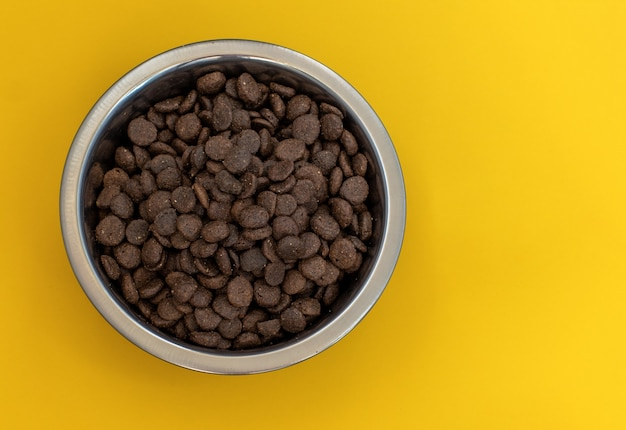 Dry brown pet food for cats or dogs in a metal bowl on a yellow