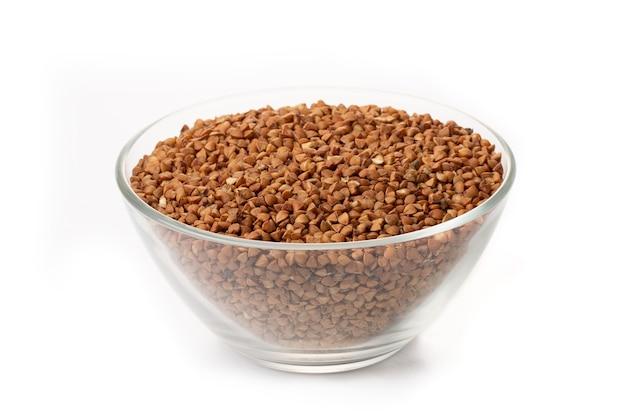 Dry buckwheat in white ceramic bowl isolated on white. spilled buckwheat.