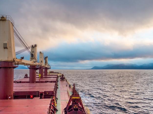 曇り空への海のデッキビューでの乾燥ばら積み貨物船