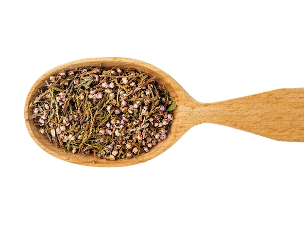 Dry calluna vulgaris in a wooden spoon isolated on a white background