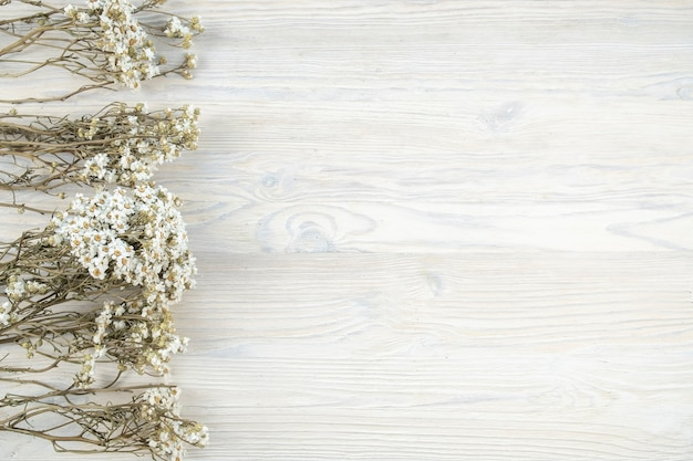 Dry camomile flowers on a wooden board. top view, copy space