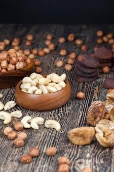 古い木製のテーブルと木製のボウルにカシューナッツを乾かし、テーブルと木の皿にカシューナッツの山を食べながら乾かします