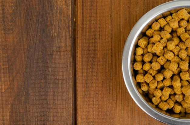 나무 배경에 금속 그릇에 마른 고양이 먹이. 스튜디오 사진