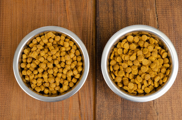 Dry cat food in metal bowl on wooden surface