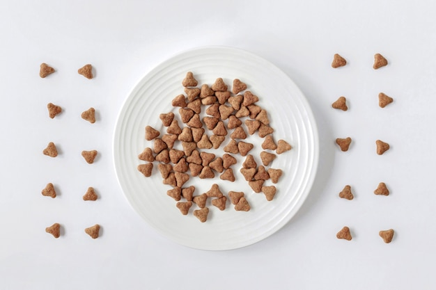 Dry cat food in a white bowl on a white background. the view from the top