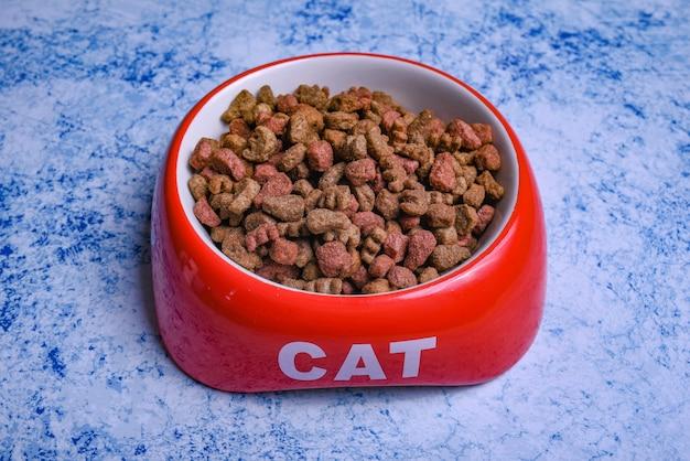 Сухой кошачий корм в ярко-красной миске.
