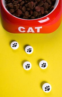 Dry cat kibble in a red bowl and white pills with picture of paw