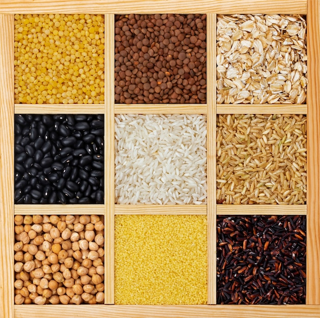 Dry cereals, groats and beans in wooden box top view
