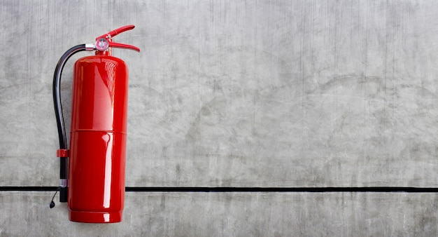 Dry chemical fire extinguisher on concrete wall background. copy space