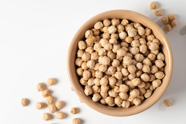 Dry chickpeas, in a ceramic dish on a white table, top view, close-up