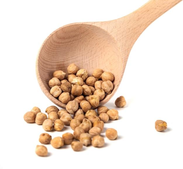 白い背景、健康食品に分離された木のスプーンで乾燥ひよこ豆