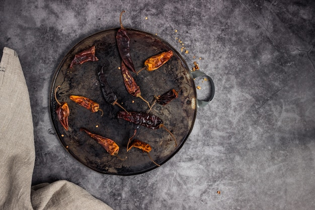Dry chillis in a comal or hotplate for being roasted with a white fabric aside