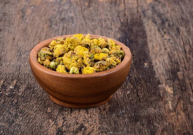Сухие хризантемы в деревянной миске на деревянном