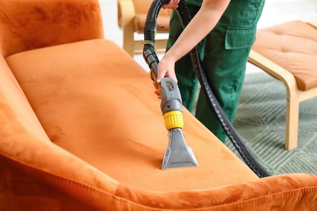 Сотрудник химчистки удаляет грязь с дивана в доме