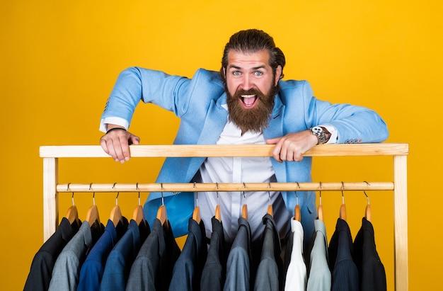 ドライクリーニングサービス。スタイルと人々のコンセプト。スーツを見て、選択するスマートカジュアルウェアのハンサムな男。ハンガーにスタイリッシュな紳士服が部屋に立っています。ビジネスファッションスタイル。