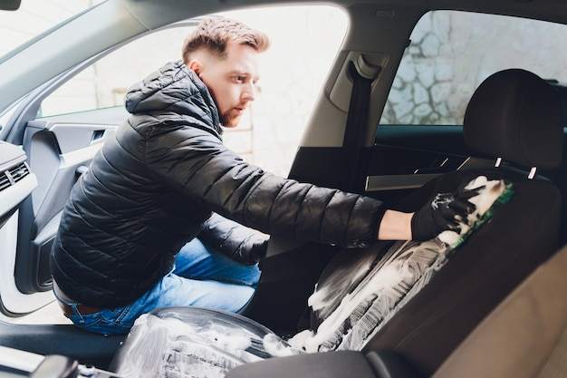 Химчистка салона автомобиля специальной пеной. концепция ухода за автомобилем. детализация автомобилей. очистка сиденья водителя с помощью профессиональных инструментов и чистящих средств.