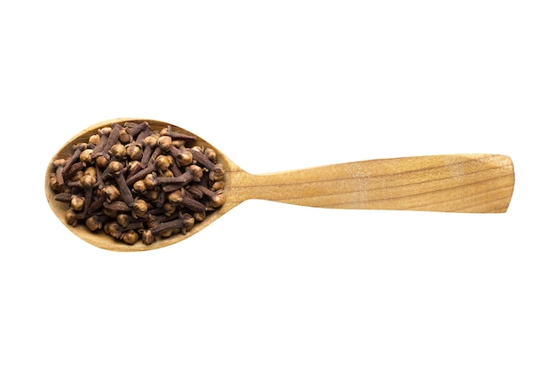 Dry cloves for adding to food. spice in wooden spoon isolated on white. seasoning of delicious meal.