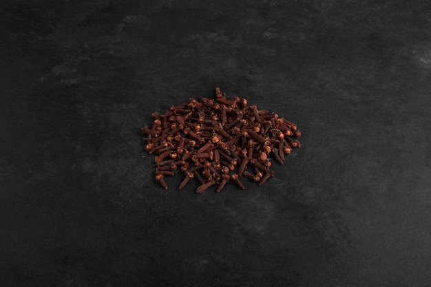 Dry cloves isolated on black surface.
