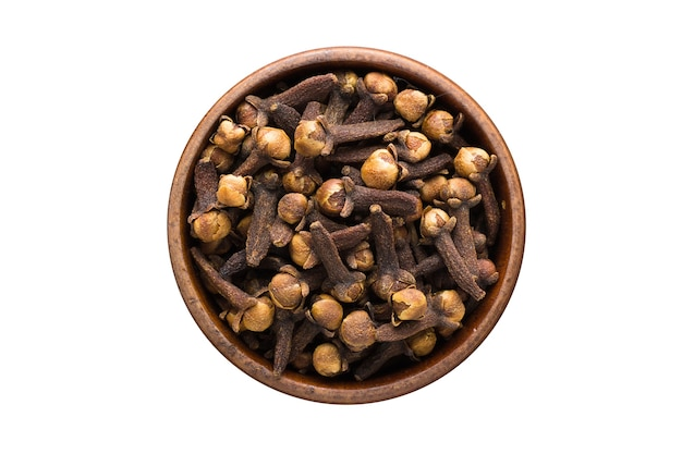 Dry cloves spice in wooden bowl, isolated on white background. seasoning top view