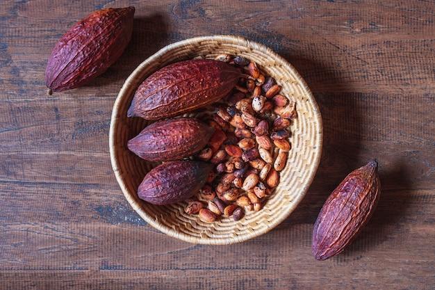 나무 배경에 바구니에 코코아 꼬투리와 코코아 콩을 건조
