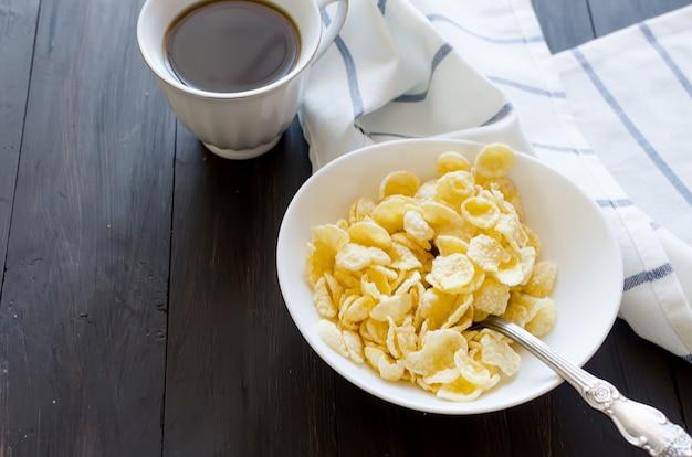 Сухие кукурузные хлопья в белой тарелке, бутылка с молоком и чашка крепкого кофе на завтрак