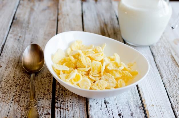 Сухие кукурузные хлопья в белой тарелке, бутылка с молоком и чашка крепкого кофе
