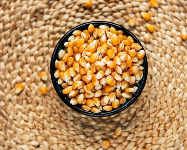Dry corn seeds in  bowl on straw mat background